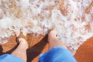 Man in flip-flops stands in sand in an ocean wave photo