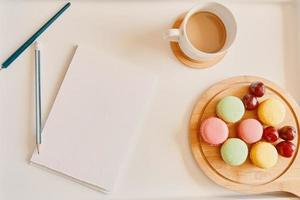 Empty notebook with cup of coffee and dessert on table photo
