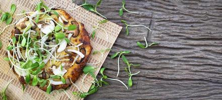 Homemade vegetarian pizza with sunflower sprouts on a wooden table background photo