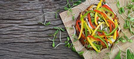 Homemade vegetable pizza with sunflower sprouts on a wooden table background photo