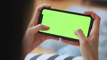Frau, die auf Smartphone mit grünem Bildschirm spielt