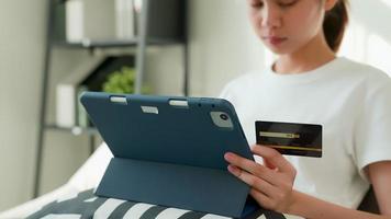 mulher segurando tablet digital e cartão de crédito