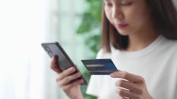 mulher segurando smartphone e cartão de crédito