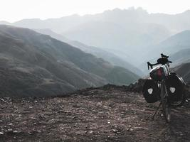 Loaded touring bicycle stands with moody dramatic panoramic mountain view and no cyclist photo