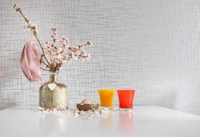 Spring daisy flowers in vase with pink facial mask hanging and raw Easter egg