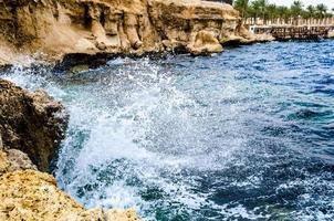 Egypt, 2021 - Splashing waves crashing against the rocks on the beach of the Red Sea