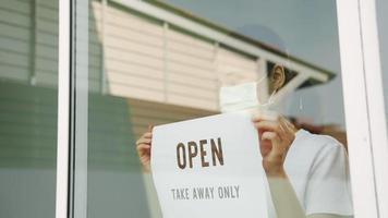 mujer pone letrero abierto en la puerta