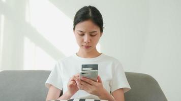 mulher segurando um smartphone e um cartão de crédito video