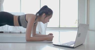 Young Lady Uses Laptop To Workout At Home video