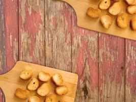 Tostadas en rodajas sobre una tabla de cortar de madera sobre un fondo de mesa de madera foto