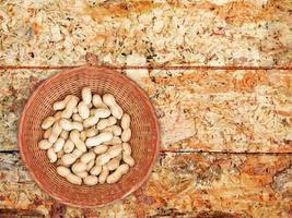 Cacahuetes enteros en un recipiente de mimbre sobre un fondo de mesa de madera foto