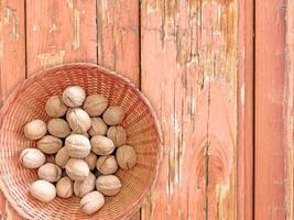 Nueces enteras en un recipiente de mimbre sobre un fondo de mesa de madera foto