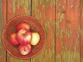 Manzanas rojas en una placa de mimbre sobre un fondo de mesa de madera foto