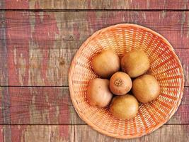 Kiwis on a wicker plate on a wooden table background photo