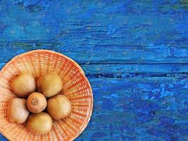 Kiwis en un plato de mimbre sobre un fondo de mesa de madera