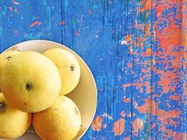 Naranjas en una placa de cerámica sobre un fondo de mesa de madera foto