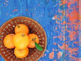 Naranjas en un recipiente de mimbre sobre un fondo de mesa de madera foto