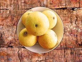 Naranjas en un recipiente de cerámica sobre un fondo de mesa de madera foto