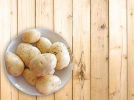 Patatas en un recipiente de cerámica sobre un fondo de mesa de madera foto