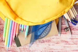 School supplies spilling out of a yellow backpack photo