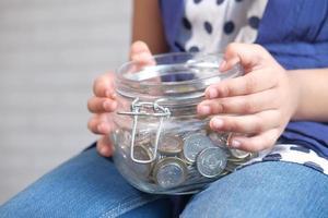 niña sosteniendo un tarro de monedas foto