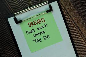 Dreams don't work unless you do written on sticky notes isolated on wooden table