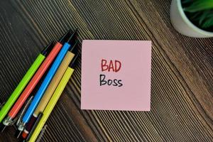 Bad boss written on sticky notes isolated on wooden table photo