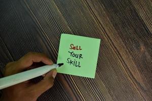 Venda su habilidad escrita en notas adhesivas aisladas sobre mesa de madera foto