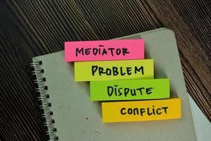 mediador, problema, disputa, conflicto- palabras escritas en notas adhesivas aisladas en la mesa de madera foto