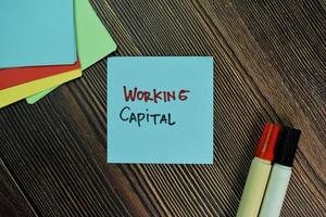 Working capital written on sticky notes isolated on wooden table photo