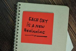 Each day is a new beginning written on sticky notes isolated on wooden table photo