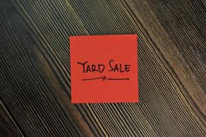 Yard sale written on sticky notes isolated on wooden table photo