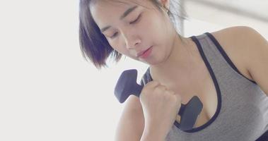 close-up de mulher asiática fazendo bíceps