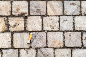 Cigarette butt on the sidewalk in the city