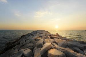 Sunset on the rocky shore of a tropical beach