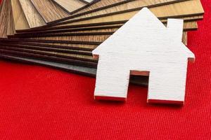 Pequeña casa de madera modelo en pila de muestra de láminas de vinilo foto
