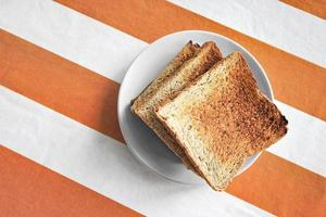 Dish with toast on tablecloth photo