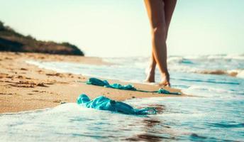 traje de baño en la arena con una mujer caminando en la playa foto