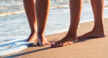dos personas caminando en la playa de cerca foto