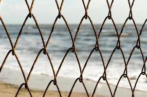 Valla de alambre de malla con un fondo de playa