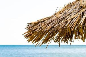 sombrilla de playa de paja contra el mar foto