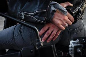 Hands of a biker hugging another biker on a motorcycle photo