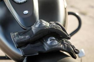 Guantes de motociclista en un asiento de motocicleta foto