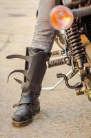 Boot of a biker with a motorcycle photo