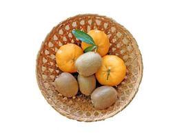 Naranjas y kiwis en un recipiente de mimbre aislado sobre un fondo blanco.