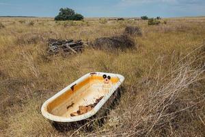 Abandoned bath tub in a field photo