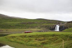 Lone red car parked near a waterfall in Iceland photo