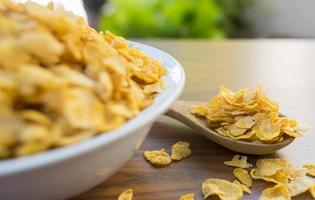 Corn flakes and bowl on wood table photo