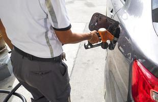 Hombre bombeando gasolina en el coche en una gasolinera foto