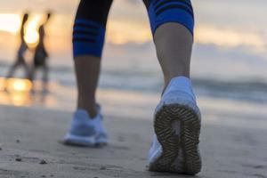 Woman running on the beach at sunrise closeup on the shoe. Patong beach, Phuket, Thailand photo